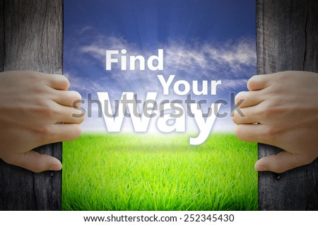 Find Your Way motivational quotes. Hand opening an old wooden door and found a texts floating over green field and bright blue Sky Sunrise. - stock photo