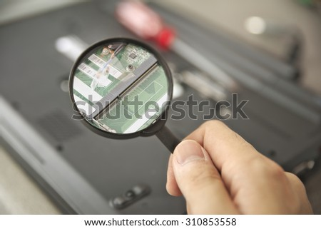 Finding computer issue by examining mainboard pcb using magnifier glass - stock photo