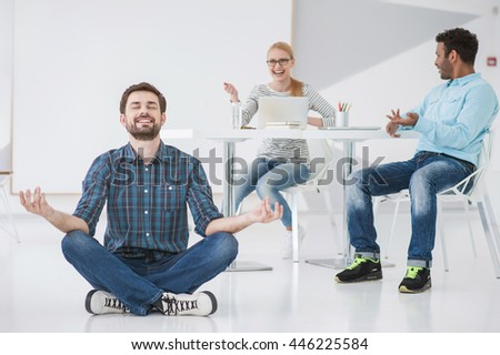 Finding his center. Smiling employee sitting on floor practicing yoga with colleague laughing at him in background