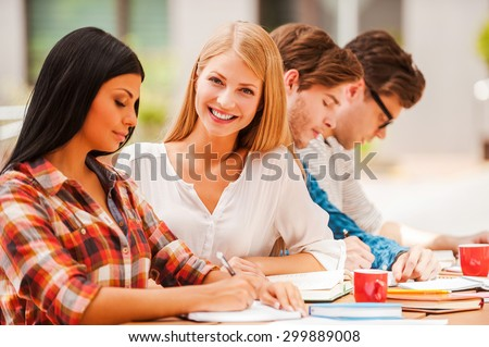 Finding inspiration in friends. Happy young woman smiling and looking at camera while sitting with her friends at the wooden desk outdoors