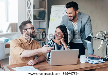 Finding solution together. Group of confident business people in smart casual wear discussing something while sitting at the desk in office - stock photo