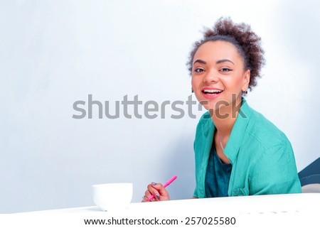 Finding the path to success. Young African woman in smart casual wear discussing something with colleagues while having a brain storming against the wall with copy space in meeting room  - stock photo