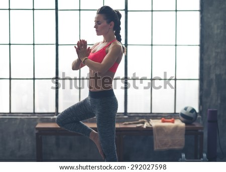 Finding the right balance, and her quiet place, a woman concentrates - eyes closed - on doing a perfect tree pose. - stock photo