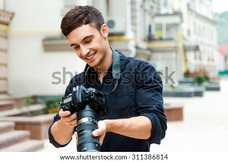 Finding the right shoot. Happy young man holding camera and smiling while standing outdoors - stock photo