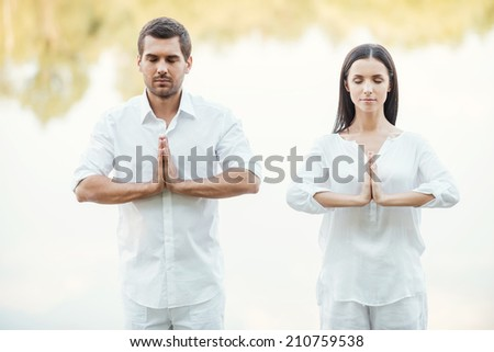 Finding tranquility. Beautiful young couple in white clothing meditating outdoors together and keeping eyes closed - stock photo