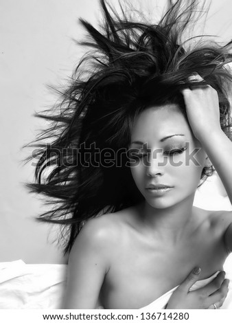 Fine art black and white photo of beautiful young woman with eyes close and wild long dark hair.