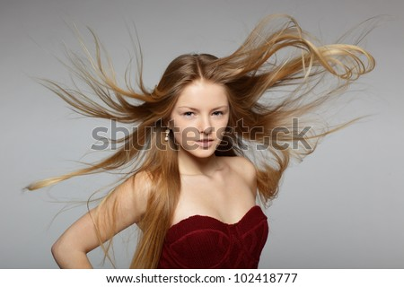 Fine art fashion portrait of blond fashion model posing with hair fluttering in the wind