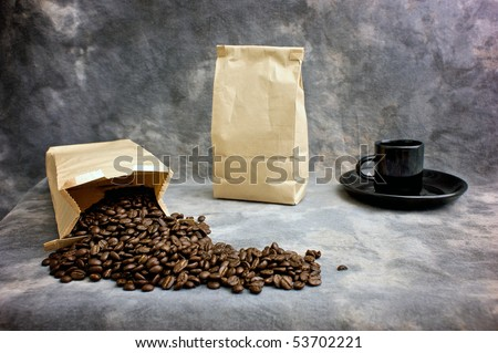 Fine art image of coffee showing a bag of whole beans, a closed bag of coffee and a black espresso cup on a saucer against a mottled studio background. Logo or text can be placed on blank bag. - stock photo