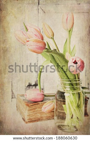 Fine art image of pink tulips in a jar next to a vintage book. Textured. - stock photo