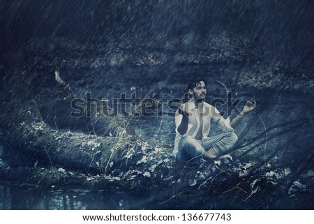 Fine art photo of a man meditating in rain