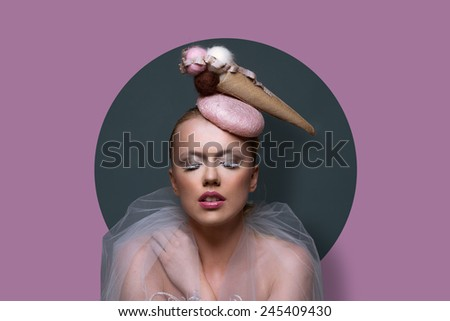 Fine art portrait of a gorgeous woman in fascinator hat in the shape of an ice cream cone with creative makeup and filmy gauze around her shoulders over a purple background - stock photo