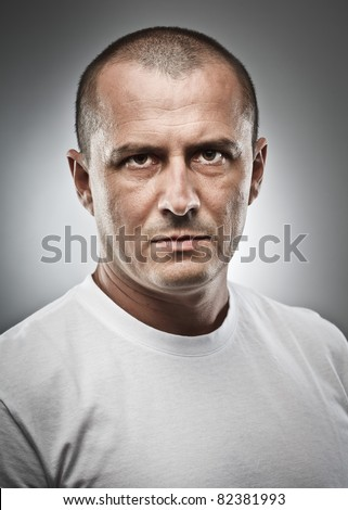 Fine art portrait of a menacing man, studio close up