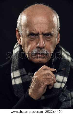 fine art portrait of an angry old man holding a pen in his hand. - stock photo