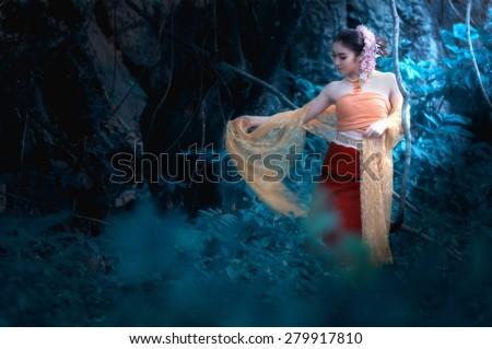 fine art portrait of thai woman wearing Thai dress in wild - stock photo