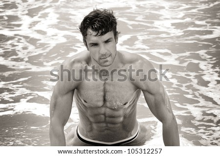 Fine art sepia toned portrait of a beautiful muscular shirtless man in the water