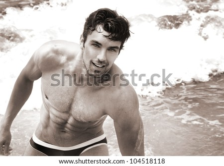 Fine art sepia toned portrait of beautiful young fit man at the beach - stock photo