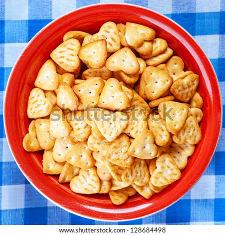 Fine biscuits in shape of heart in red plate on blue checkered tablecloth. - stock photo