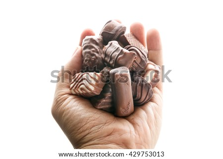 fine chocolates in white, dark, and milk chocolate in a hand