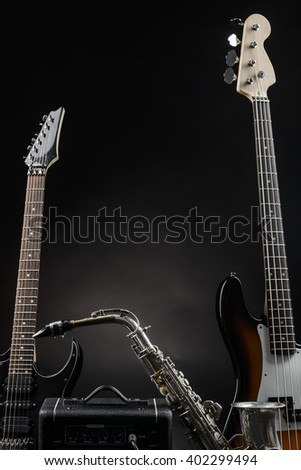 Fine composition made of musical instruments. Alt saxophone, bass and electric guitars, guitar amp. Black background. - stock photo