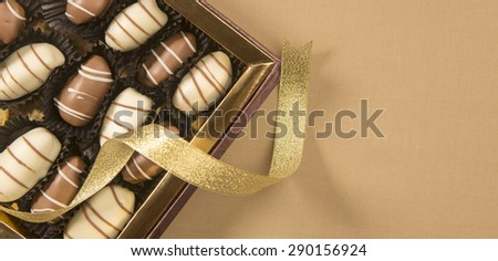Fine date chocolates in a golden box with loose ribbon wrapped around. - stock photo