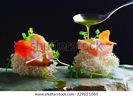 Fine dining, fresh raw ahi tuna sashimi served on sponge with herbs - stock photo
