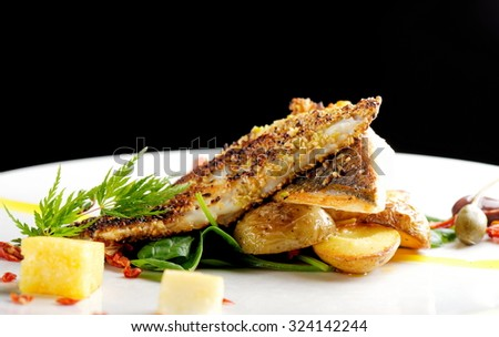 Fine dining, Seabream fish fillet breaded in herbs and spice with potato and vegetable - stock photo