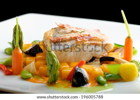 Fine dining, White fish fillet breaded in herbs and spice with grilled bacon and vegetables - stock photo