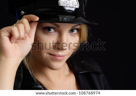 Fine girl in a uniform of  police officer on a black background - stock photo