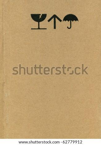 Fine image close-up of grunge black fragile symbol on cardboard - stock photo