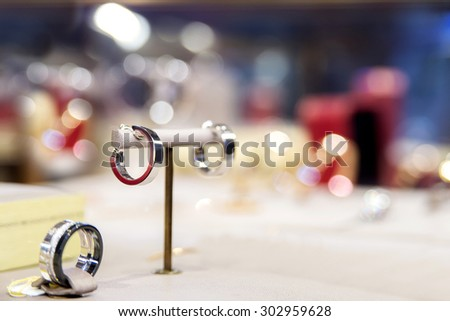 Fine luxury platinum ring in jewelry window display of luxury jewelry boutique with glitter background - stock photo
