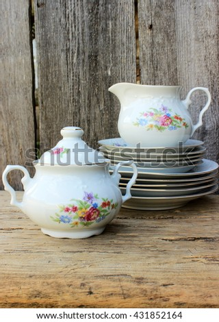Fine porcelain dinner ware set decorated with floral pattern on old grunge wooden background. Vintage kitchen ware in a rustic setting - stock photo