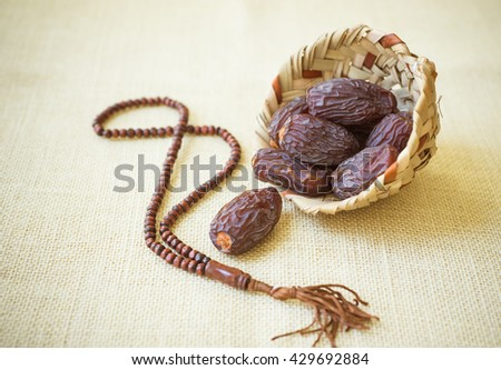 Fine quality Mejdool dates in a earthen basket with wooden islamic rosary. - stock photo