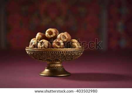 Fine quality ripen dates and an vintage plate. An ornamental bowl of Arabian dates. - stock photo