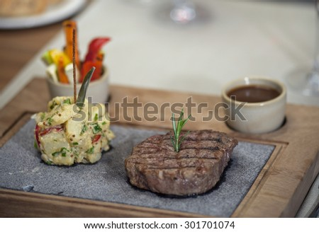 Fine restaurant dinner table place setting: napkin, wineglass, plate and beef - stock photo