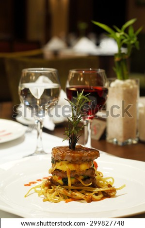 Fine restaurant dinner table place setting: napkin, wineglass, plate, beef and wine - stock photo