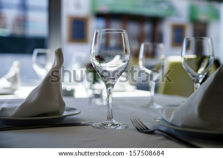 Fine restaurant dinner table setting by wineglass and napkin