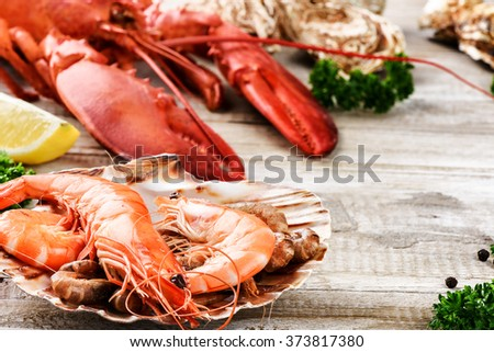 Fine selection of crustacean for dinner. Lobster, jumbo shrimps and oysters on old wooden table - stock photo