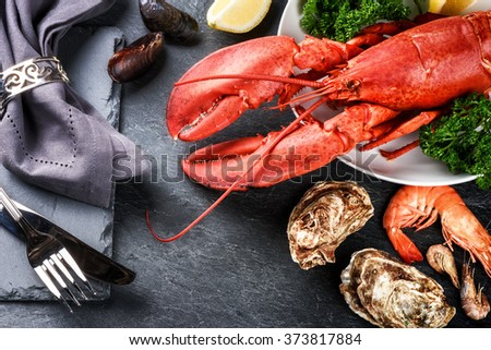 Fine selection of crustacean for dinner. Lobster, oysters and shrimps on dark background - stock photo