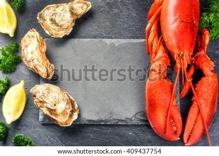 Fine selection of crustacean for dinner. Steamed lobster and oysters on dark background - stock photo