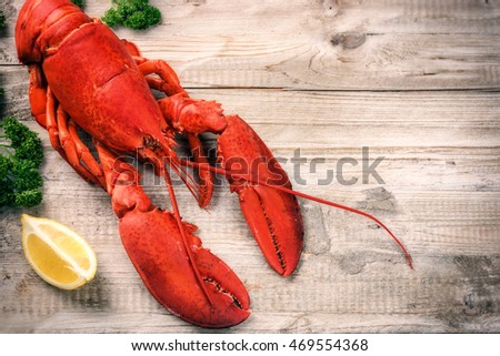 Fine selection of crustacean for dinner. Steamed lobster with lemon on wooden  background