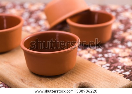 Fine solid clean natural crockery bowls dishware standing on wooden cutting board indoor on floral background closeup, horizontal picture - stock photo