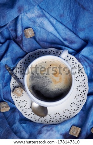 Fine white porcelain cup of frothy black coffee on a vintage lacy saucer with a silver teaspoon, on blue velvet next to brown sugar cubes, shot from high-angle - stock photo