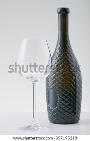 Fine wine. Wine glass and bottle of beverage are standing on white surface.  - stock photo