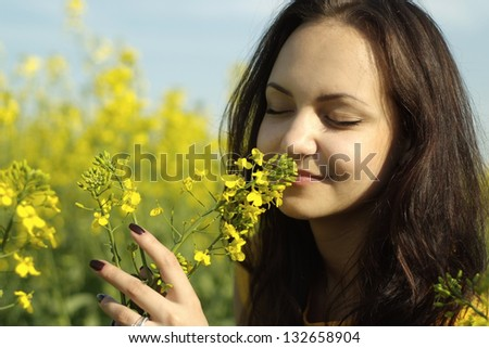 Fine young girl in the middle of a field of yellow flowers