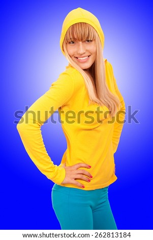 Fine young woman in yellow jacket, on blue background. - stock photo
