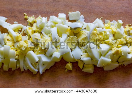 finely chopped boiled eggs in the middle of an old wooden cutting board close-up view from above - stock photo
