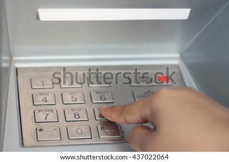 Finger about to press a pin code on a pad.