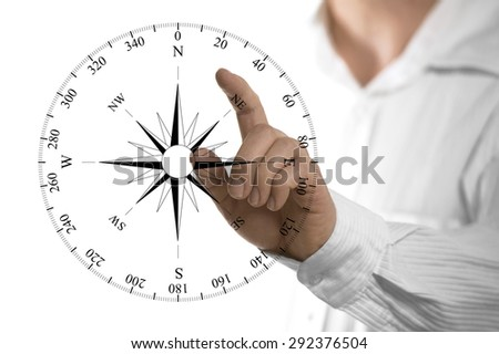 Finger about to touch a compass rose over white background. Concept of orientation. - stock photo