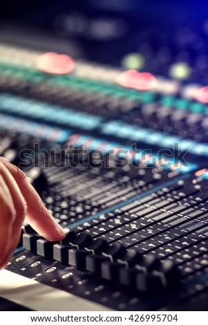 Finger adjusting audio mixer in studio - stock photo