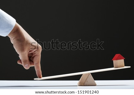 finger and small house on a Teeter-board